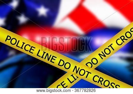 Yellow Police Tape With Sign Text: Police Line Do Not Cross On Blurred Defocused Silhouette Of Ameri
