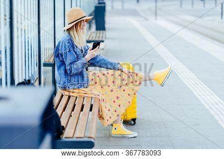 Blond Woman Traveler In Straw Hat, Denim Jacket, Summer Dress Sitting On Bus Or Tram Stop. Tourist S