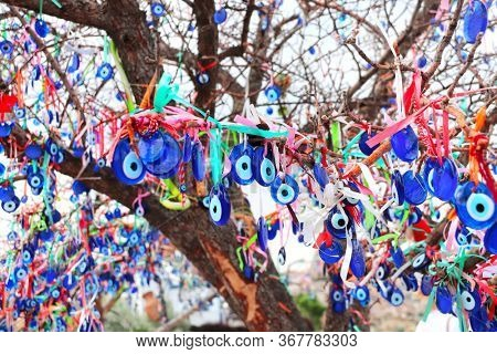 Many glass mascots - evil eye charms hang from a tree in Pigeon Valley, Cappadocia, Turkey