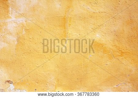 Grunge background with old stucco wall texture of yellow color