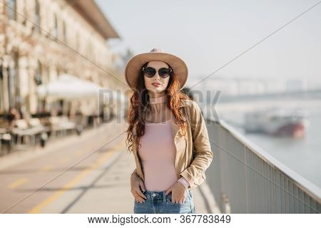 Gorgeous Young Woman In Dark Sunglasses Standing In Confident Pose At Embankment. Outdoor Photo Of G