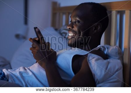 Side View Portrait Of Smiling African-american Man Using Smartphone In Bed At Night, Copy Space