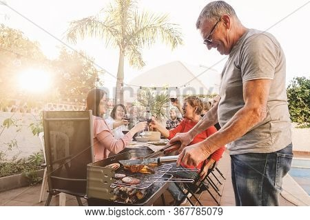 Happy Family Cheering And Toasting With Red Wine In Barbecue Party - Chef Senior Man Grilling Meat A