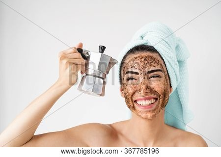 Young Smiling Woman Applying Coffee Scrub Mask On Face - Happy Girl Having Healthy Skin Care Spa Day