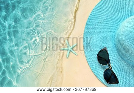 Summer Hat With Sunglasses. Top View, Summer Concept Over A Tropical Beach Background.