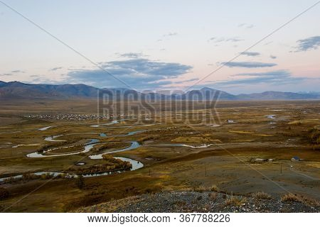 Top View Of The Altai Russian Village Of Ortolyk, The Steppe And Altai Mountains At Sunset, The Chuy
