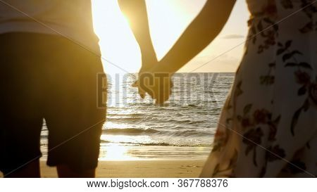 Silhouette Of Young Family Running Joining Hands On Beach To Boundless Ocean Against Sunset On Horiz
