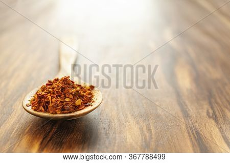 Crushed Hot Red Cayenne Peppers On A Wooden Spoon. Horizontal Photo With Plenty Of Empty Space.