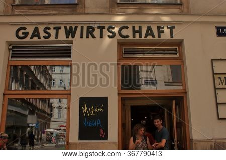 Wien, Austria- Aug 2019: Two Persons Exit From A Grocery Store. Hires.