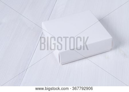White Box On Wooden White Table. Stock Photo. White Box Mockup For Product And Advertising With Cove