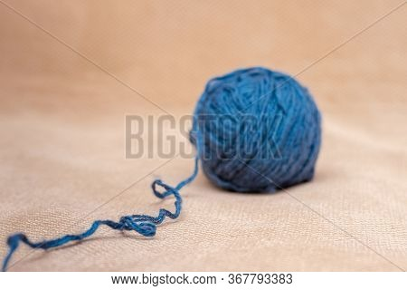 A Skein Of Blue Yarn For Knitting On An Orange Fabric