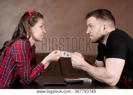A Man And A Woman Are Trying To Take Money From Each Other. A Comic Form Of Sharing A Family Budget