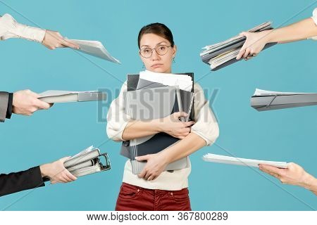 A Sad Girl Holds A Bunch Of Documents In Her Arms, Employees Hands Hold Out Additional Folders And D
