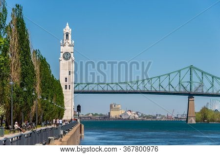 Montreal, Ca - 23 May 2020: Montreal Clock Tower And Jacques Cartier Bridge In Spring