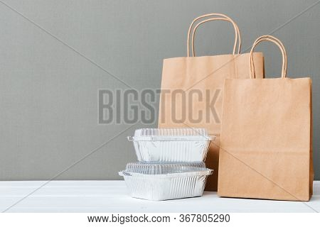 Paper Bags And Food Containers On White Table Gray Background. Food Delivery Service. Takeaway Food