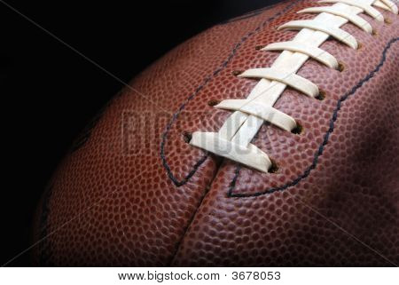 a leather football on a black background poster