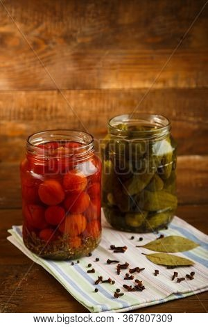 Jars Of Pickled Homemade Pickled Cherry Tomatoes Gherkins On A Wooden Table.