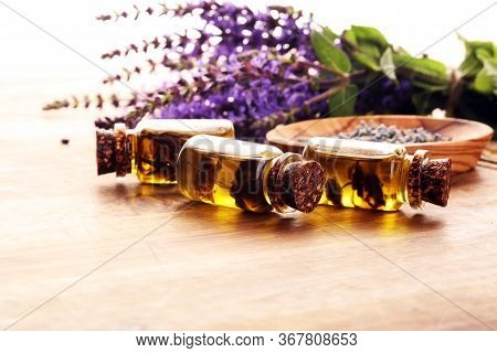 Lavender Herbal Oil And Lavender Flowers. Bottle Of Lavender Massage Oil For Aromatherapy Treatment