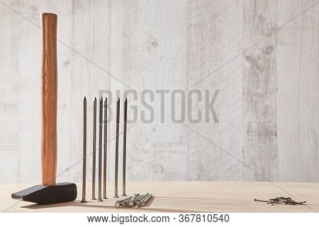 Hammer Tool On Wooden Table. Different Sizes Of Tacks. Renovation And Construction Site. Copy Space.