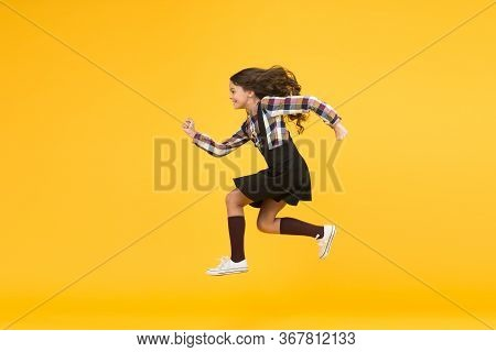Unstoppable Future. Happy Girl In Midair Yellow Background. Energetic Child Run To School. Pursuing