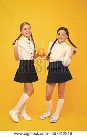 Proud Of Healthy Hair. Cute Small Children With Plaited Hair Drinking Natural Juice On Yellow Backgr