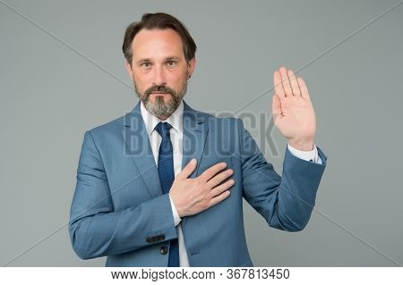 I Swear. Senior Lawyer Make Oath Grey Background. Mature Man Hold Hand On Heart And Open Palm. Pledg