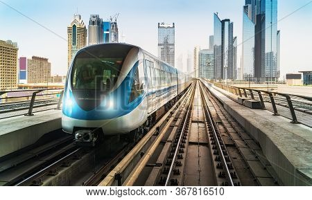 Dubai Metro Train On Rails At Background Of Skyscrapers. Famous Outdoor Subway Red Line.