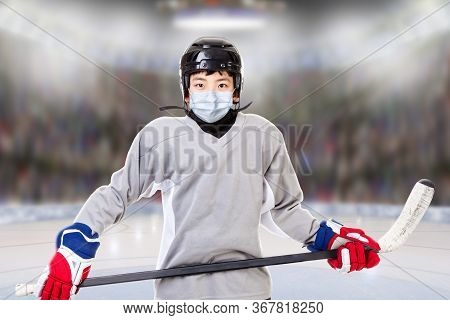 Junior Ice Hockey Player With Full Equipment And Sports Uniform Posing In Fictitious Arena With Face