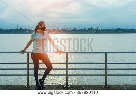 Young Fitness Asian Woman Standing Resting Tired With Wearing A Protective Mask Covid-19 After Runni