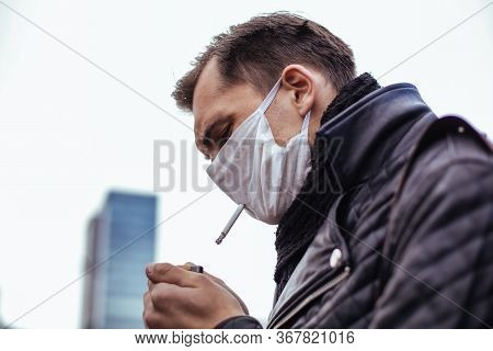 Serious Man In A Protective Mask Smokes Standing On The Street.