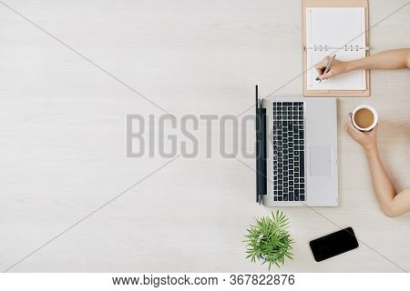 Female Freelancer Working At Big Office Table, Drinking Coffee And Taking Notes In Planner