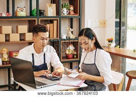 Young Cafe Owners Sitting At Table, Checking Bills And Paying Online
