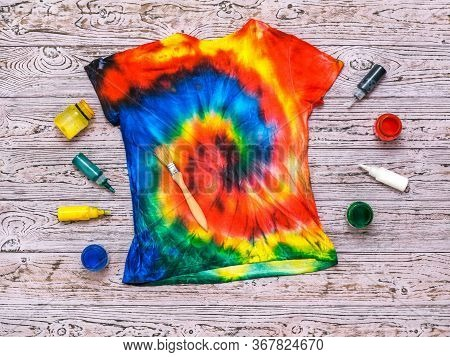 T-shirt Painted In The Style Of Tie Dye With Colors On A Wooden Background. White Clothes Painted By