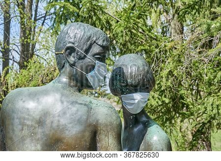 Laval, Canada - May 17, 2020: Statue Of A Man And Woman With Protective Surgical Mask On Them In Cen