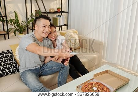 Happy Young Vietnamese Couple Eating Pizza, Drinking Beer And Watching Tv At Home