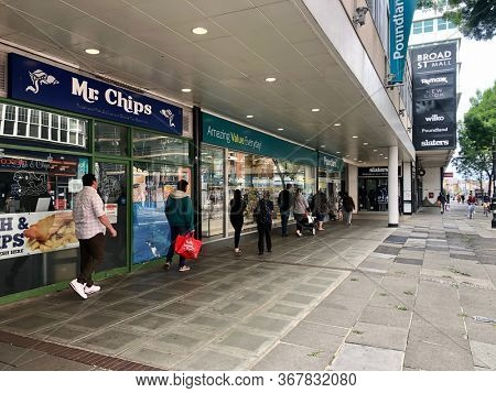 READING, UK - MAY 24, 2020: Customers queue to enter a Poundland shop while respecting social distancing rules during the Coronavirus Pandemic in Reading, Berkshire, UK.