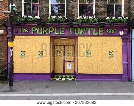 READING, UK - MAY 24, 2020: The Purple Turtle pub, a well know local establishment, is boarded up with wood to prevent looting during the Coronavirus pandemic in Reading, Berkshire, UK.