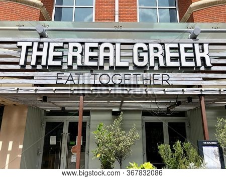 READING, UK - MAY 24, 2020: Outside an outlet of The Real Greek, a chain of Greek restaurants, in Reading, Berkshire, UK.