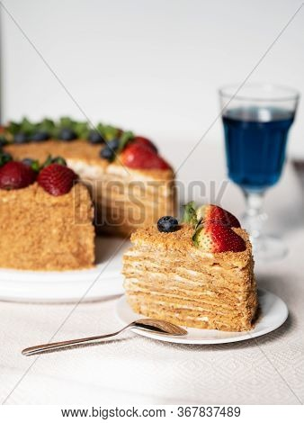 Vertical Photo, A Slice Of Cake On A Plate, Honey Cake Decorated With Strawberries And Blueberries O