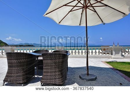 Vacation In Vietnam. On The Promenade, In The Shadow Of An Umbrella, Are A Table And Wicker Chairs.