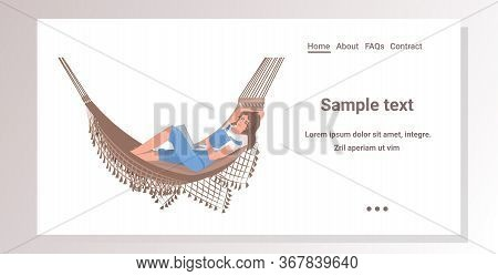 Woman Lying In Hammock Using Laptop Working At Home During Coronavirus Quarantine Self-isolation Fre
