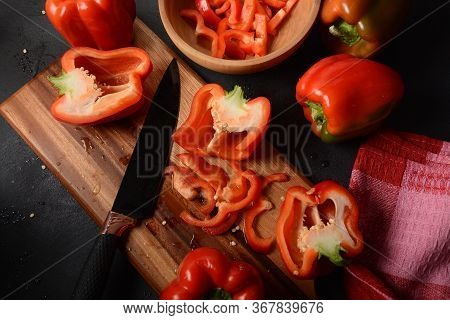 Cutting Red Sweet Bell Pepper On Wooden  Kitchen Board With Knife. Salad Or Food Preparing. Chef Coo
