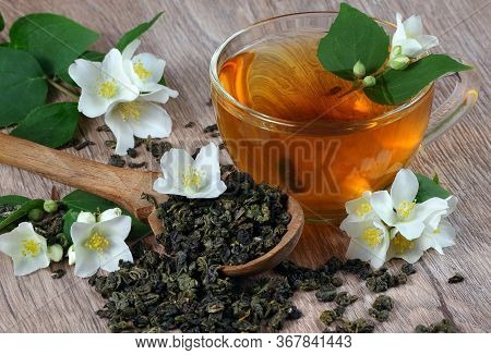 Green Tea With Jasmine. Dry Green Tea Leaves With Jasmine Flowers In A Wooden Spoon And A Cup Of Tea
