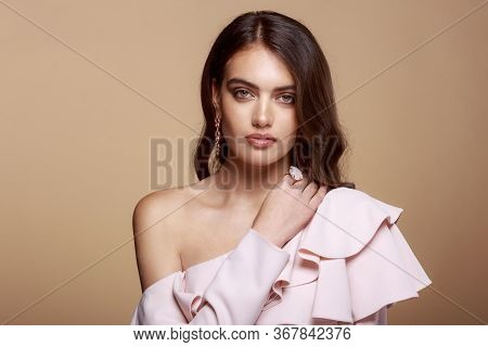 Frontal Portrait Of A Woman Dressed In Pink Dress With Bare Shoulder, Brown Wavy Hair, Model Charm W