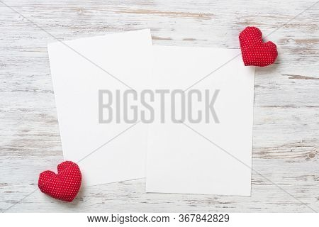 Blank Sheets Of Paper And Red Love Hearts On Wooden Table. View From Above On Romantic Composition W