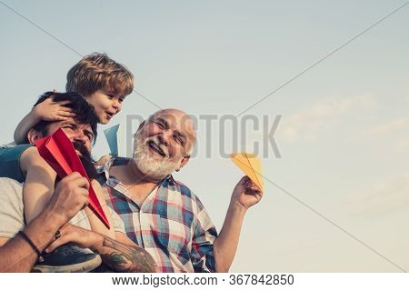 Men Generation. Happy Child Playing With Toy Paper Airplane Against Summer Sky Background. Cute Son