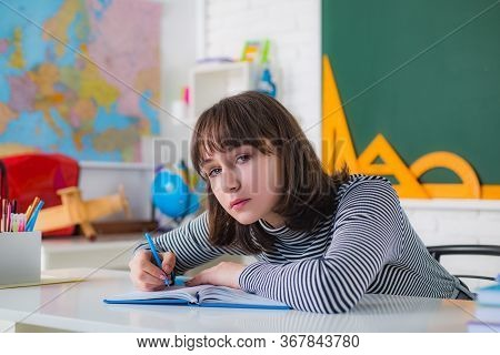 Teenager Girl Drawing Picture In Class. Close Up Face. Teenager Is Learning In Class On Background O