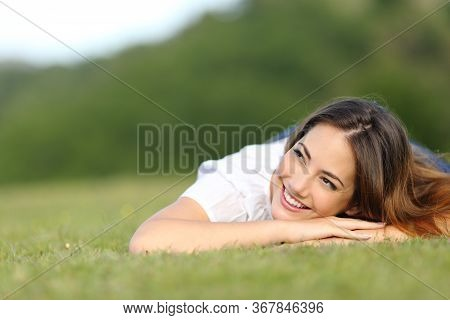 Happy Woman Thinking Lying On Green Grass Looking Sideways On A Park At Summer