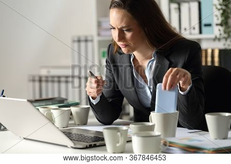 Overworked Executive Woman Makes Mistakes Due To Exhaustion With Several Coffee Cups Sitting In The