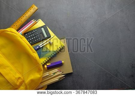 Top View Of School Bag With School Suppliers On Table